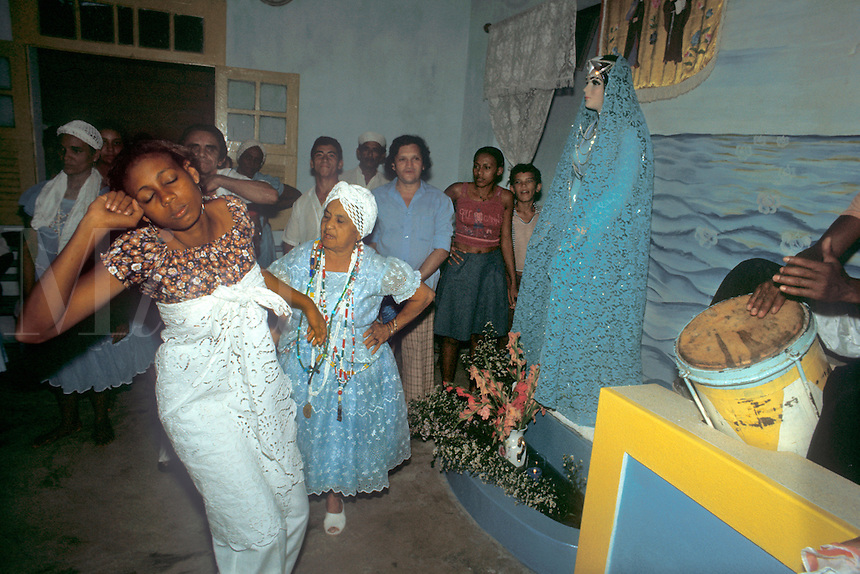 Afro-Brazilian spirit possession cult in Belem, Para, Brazil. Girl spectator and believer is in trance, possessed by a spirit, to the sound of drums. The mae de santo or cult leader is watching, ready to attend the spirit