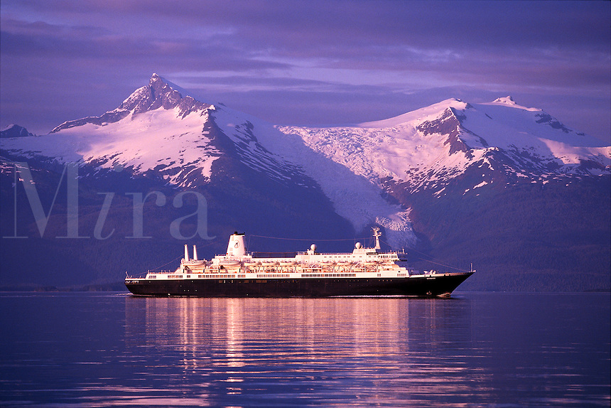 A tour ship explores the tranquil waters of the Inside passage in SE Alaska at sunset.