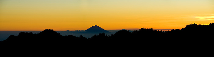 Panoramic Landscape Photo of Mount Agung on Bali, Silhouetted at Sunset from Mount Rinjani, Lombok, Indonesia. Mount Agung (Gunung Agung) is the highest vocano on Bali, and the view of it sitting just above the Mount Rinjani crater rim, silhouetted at sunset from the second night campsite of the Three Day Mount Rinjani Trek gives a fantastic perspective.