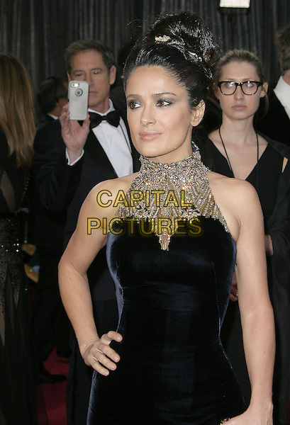 Salma Hayek (wearing McQueen).85th Annual Academy Awards held at the Dolby Theatre at Hollywood & Highland Center, Hollywood, California, USA..February 24th, 2013.oscars half length black dress gold embellished jewel encrusted high collar sleeveless hand on hip hair up bun.CAP/ADM.©AdMedia/Capital Pictures.
