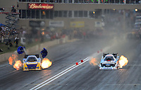 Jul, 20, 2012; Morrison, CO, USA: NHRA funny car driver Ron Capps (left) races alongside Courtney Force during qualifying for the Mile High Nationals at Bandimere Speedway. Mandatory Credit: Mark J. Rebilas-US PRESSWIRE