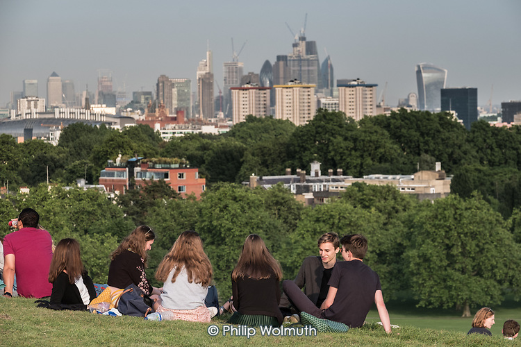 Group of young people relax on Primrose Hill, overlooking highrise blocks in Docklands and the City of London.