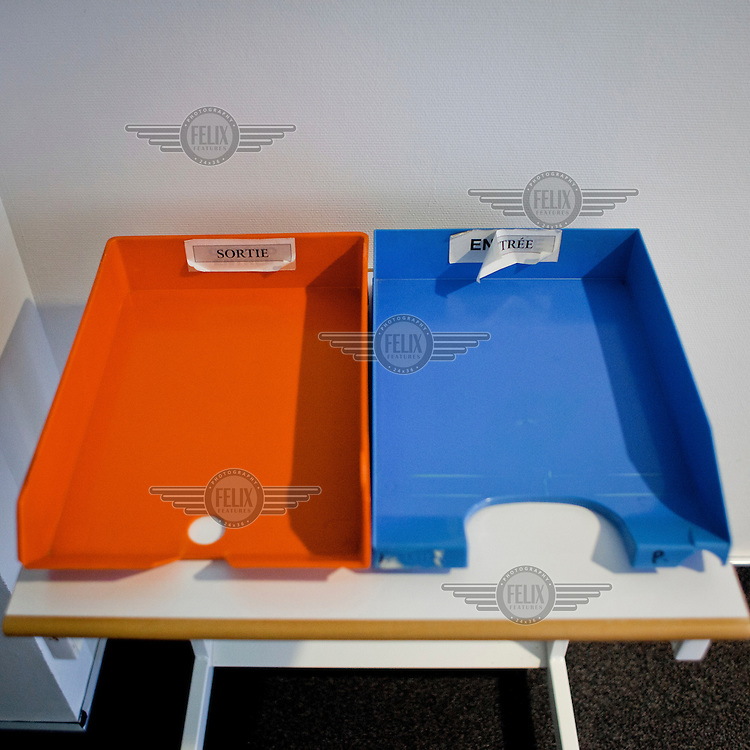 As yet unused 'in' and 'out' document trays at the European Parliament. Every month thousands of the parliament's employees travel back and forth between the three sites of European government, Brussels, Strasbourg and Luxembourg, bringing huge quantities of paperwork with them.