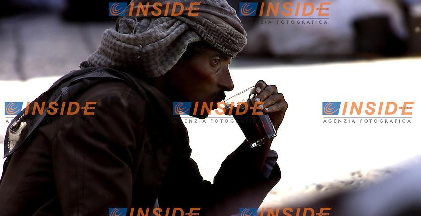 """Yemen, Gennaio 2006..San'a, la città vecchia della capitale fatta di vicoli e di suq e' stata dichiarata tra i siti protetti dall'Unesco...Nella foto:  Ritratto di un anziano yemenita mentre sorseggia il te', lo shai (te') e' la bevanda più diffusa dello Yemen ed e' sostitutiva dell'acqua.....Portrait of an old men drinking """"shai"""", the most common drinking in Yemen.......Photo Antonietta Baldassarre Insidefoto(www.insidefoto.com)"""