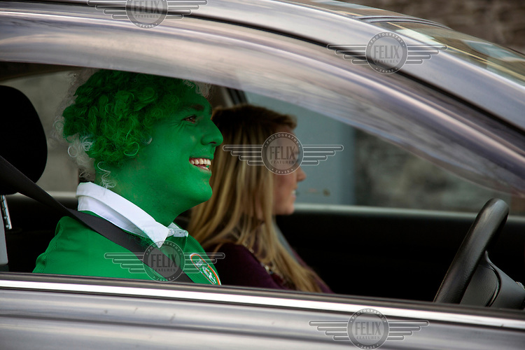 A man with green face paint arrives at Lansdowne Road stadium to watch the Irish national football team play a match against Poland.