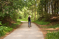 A woman in a sun hat bikes the forested trails of Mackinac Island in Michigan.