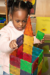 Education preschool 3-4 year olds girl building tower with magnetic tiles