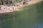 A fly Fisherman on the bank of Lake Taneycomo that flows downstream from the Table Rock Dam Missouri