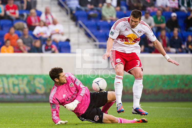 Kenny Cooper (33) of the New York Red Bulls deflects a clearance by Houston Dynamo goalkeeper Tally Hall (1) in for the game's only goal during the first half of a Major League Soccer (MLS) match at Red Bull Arena in Harrison, NJ, on May 09, 2012.