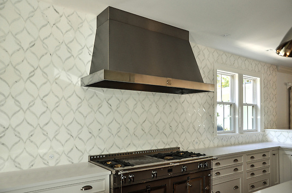 This custom kitchen backsplash features Sophie, a handmade mosaic shown in polished Calacatta Tia and honed Thassos from the Silk Road Collection by Sara Baldwin for New Ravenna.<br />