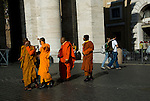 buddhist monks walk on the saint peter square in rome italy