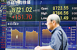 June 18, 2012, Tokyo, Japan - A man walks past the stock market board showing the figure for the Nikkei 225 in downtown Tokyo. The Nikkei 225 climbed 151.70 points to 8,721.02 at Tokyo's 3pm closing. Greece's positive election vote helped ease fears that the country may fall out from the euro currency. (Photo by Christopher Jue/AFLO)