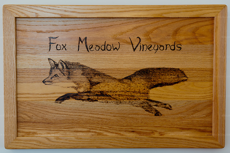 A wood-burned sign hangs near the door in the Winery at Fox Meadow.