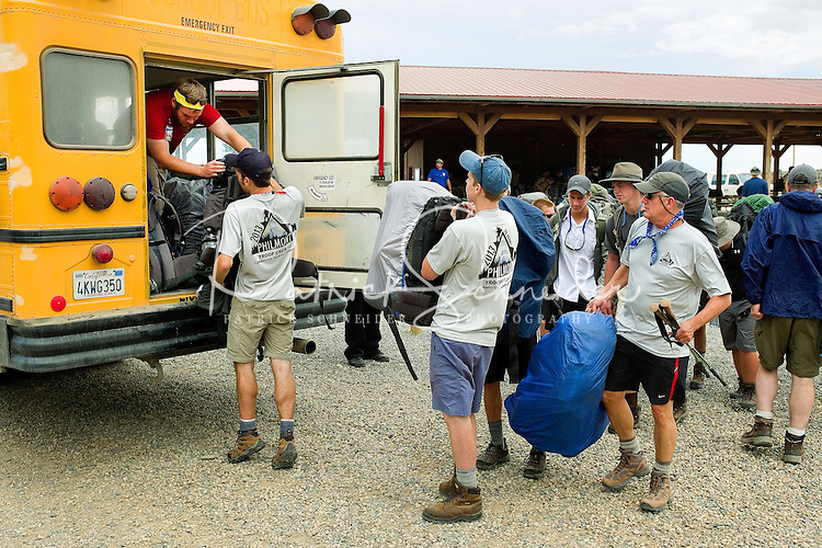 Photo story of Philmont Scout Ranch in Cimarron, New Mexico, taken during a Boy Scout Troop backpack trip in the summer of 2013. Photo is part of a comprehensive picture package which shows in-depth photography of a BSA Ventures crew on a trek. In this photo a BSA Venture Crew works to load their backpacks on to a school bus for the short ride to the backcountry drop off point at the Philmont Scout Ranch. <br /> <br /> Photo by travel photograph: PatrickschneiderPhoto.com