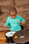 Two year old toddler boy hitting drums with drumsticks