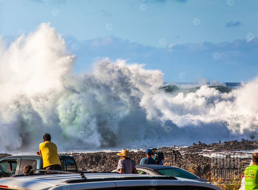 Spectators watch giant waves crashing against rocks during a large winter swell at Shark's Cove, North Shore, O'ahu.