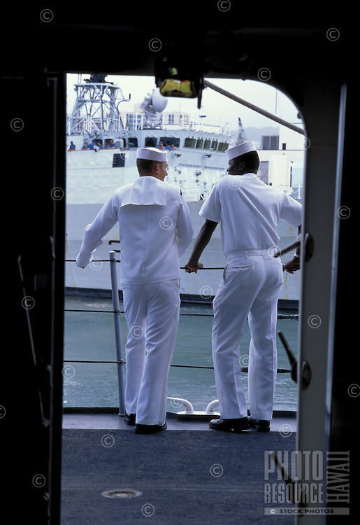 Two sailors stand by the guardrail on a Navy ship.