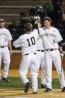 Nate Mondou (10) of the Wake Forest Demon Deacons is meet at home plate by teammate Evan Stephens (5) after hitting a home run against the High Point Panthers at Wake Forest Baseball Park on April 2, 2014 in Winston-Salem, North Carolina.  The Demon Deacons defeated the Panthers 10-6.  (Brian Westerholt/Four Seam Images)
