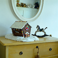 An iced gingerbread house decorated with coloured Smarties is one of several Christmas decorations in a child's bedroom