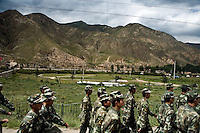 Chinese military police march in formation past grasslands outside of Xiahe, Gansu, China. Xiahe, home of the Labrang Monastery, is an important site for Tibetan Buddhists.  The population of the town is divided between ethnic Tibetans, Muslims, and Han Chinese.