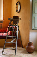 Old leatherbound books are stacked on a ladder in a corner of the living room