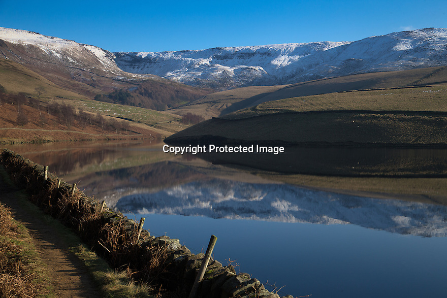 """20/01/16<br /> <br /> Kinder Scout reflected in Kinder Reservoir.<br /> <br /> Only 160 miles, as the crow flies from central London, Will Flanagan (36), explores the stunning icicles at Kinder Downfall near Hayfield in the Derbyshire Peak district today. After days of cold sub-zero temperatures the 100 ft waterfall finally froze over last night.<br /> <br /> Will said: """"I had to set off at dawn to to get up here. I've been watching the overnight temperatures and thought there's be a chance it would be frozen today. <br /> <br /> """"As the sun began to rise the ice started to melt. I could here it cracking beneath my feet and I saw a few giant icicles crash down. So I didn't stay up there very long!<br /> <br /> """"I definitely wouldn't have wanted to climb any higher up it today even if I'd had ropes with me - the ice wouldn't have been strong enough to support me. If I'd have arrived any later I wouldn't have risked going all the way up. <br /> <br /> """"But all the same it was an awesome spectacle and one of the most extreme walks I've ever done.""""<br /> <br /> The waterfall flows from Kinder Scout the only mountain in the Derbyshire Peak District between Hayfield and Edale. <br /> <br /> All Rights Reserved: F Stop Press Ltd. +44(0)1335 418365   www.fstoppress.com."""