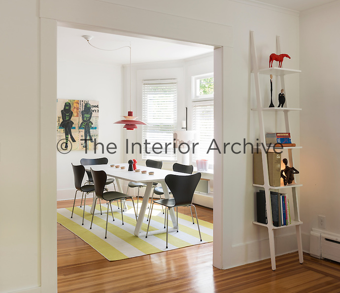 A view through an open doorway to a modern, white dining room with a wood floor. The room is furnished with a white Thomas Eriksson table and black Arne Jacobsen butterfly back chairs. A ladder shelf to one side displays ceramics and books.