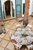 A round stone table is laid for an alfresco lunch on the paved courtyard patio.