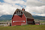 Red wooden barn with gambrel roof and weather vane at top of ventilator beneath Oregon's Blue Mountains.