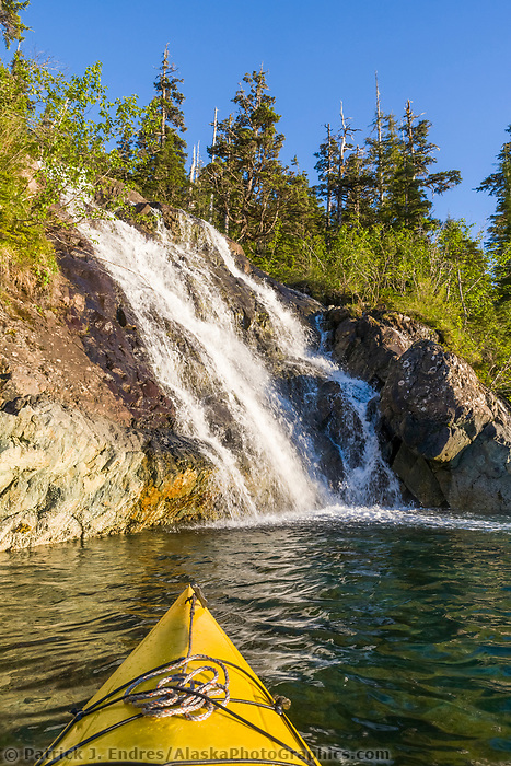 Sea kayaking by a waterfall in Copper Bay, Knight Island, Prince William Sound, Alaska
