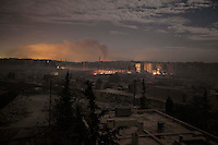 In this Saturday, Dec. 01, 2012 photo, smoke rises during heavy shelling in Bustan Al-Pasha district at night as the fog falls on the cold streets of Aleppo, the Syrian's largest city. (AP Photo/Narciso Contreras)