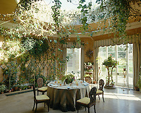 Conservatory dining room with a glass domed ceiling overgrown with plants