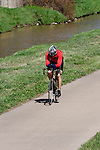 Caucasian man biking along Cherry Creek in Denver, Colorado. .  John offers private photo tours in Denver, Boulder and throughout Colorado. Year-round.