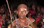 Lolgorian, Kenya. Siria Maasai Manyatta; newly shaved moran wearing ceremonial cowhide cloak looking sad and serious.
