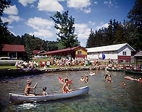 People having fun in water in canoes on floats and at the dock. 1965 photograph.