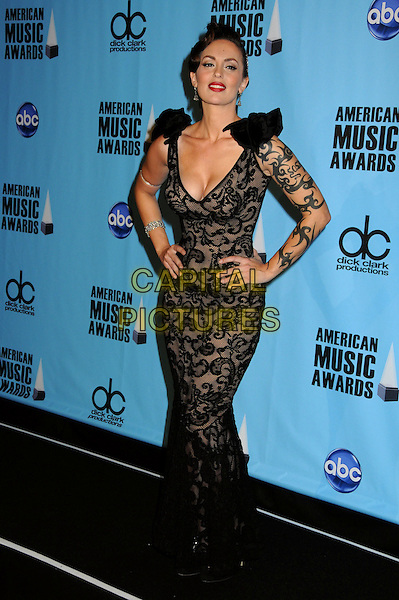 DEBORAH EPSTEIN aka SoShy.At the 2009 American Music Awards - Press Room held at the Nokia Theatre L.A. Live, Los Angeles, California, USA, .22nd November 2009..AMA AMAs full length black lace long maxi dress tattoo arm hands on hips sleeveless shoulders fishnet cleavage low cut plunging neckline .CAP/ADM/BP.©Byron Purvis/AdMedia/Capital Pictures.