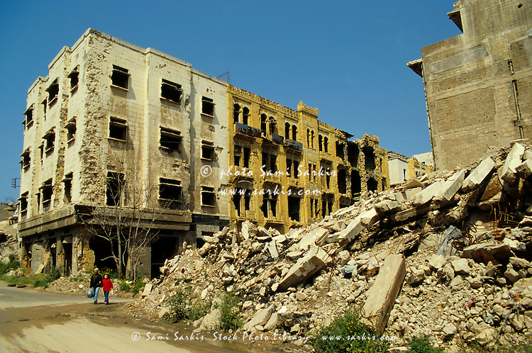 People walking past apartment buildings destroyed by the Lebanese Civil War, Beirut, Lebanon.