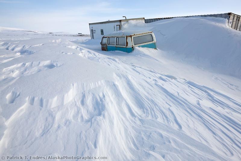 Wind blown and drifted snow encloses an old van along the coast of Nome, Alaska, on the Seward Peninsula