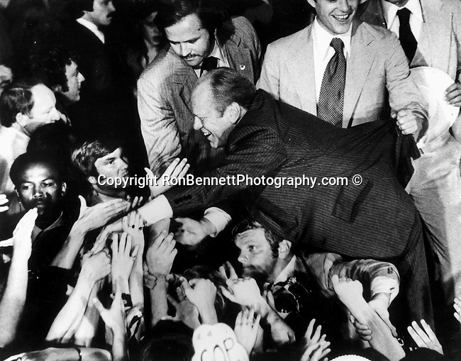 President Gerald Ford goes into crowd shaking hands during campaign, President Gerald Ford, President and Betty Ford second son, John &quot;Jack&quot; Gardner Ford hold coat of President Gerald Ford from falling in crowd during campaign, <br />