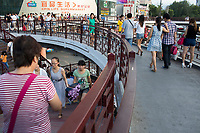 People walk in a pedestrian overpass in Xian, Shaanxi, China.