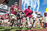 Florida State interim head coach Odell Haggins and offensive lineman Rick Leonard take the field before an NCAA college football game against Louisiana Monroe in Tallahassee, Fla., Saturday, Dec. 2, 2017.  (AP Photo/Mark Wallheiser)