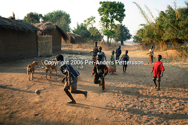 MPHANDULA, MALAWI - AUGUST 18: Unidentified boys play soccer on August 18, 2006 in Mphandula village, about 30 miles outside Lilongwe, Malawi. Mphandula is a poor village in Malawi, without electricity or clean water. Nobody owns a car or a mobile phone. Most people live on farming. About 7000 people reside in the village and the chief estimates that there are about five-hundred orphans. Many have been affected by HIV/Aids and many of the children are orphaned. A foundation started by Madonna has decided to build an orphan center in the village through Consol Homes, a Malawi based organization. Raising Malawi is investing about 3 million dollars in the project and Madonna is scheduled to visit the village in October 2006. Malawi is a small landlocked country in Southern Africa without any natural resources. Many people are affected by the Aids epidemic. Malawi is one of the poorest countries in the world and has about 1 million orphaned children. (Photo by Per-Anders Pettersson)
