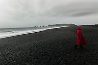 Reynisdrangar, Iceland - A tourist walks on a black sand beach in Reynisdrangar, Iceland, March 2016.  Reynisdrangar are basalt sea stacks situated under the mountain Reynisfjall near the village Vík í Mýrdal, southern Iceland which is framed by a black sand beach that was ranked in 1991 as one of the ten most beautiful non-tropical beaches in the world.