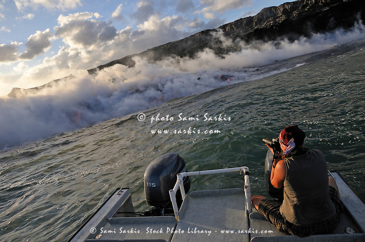 Woman on boat photographing steam rising off lava flowing into ocean, Kilauea Volcano, Hawaii Islands, United States