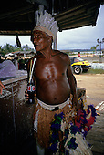 Coroa Vermelha, Bahia State, Brazil; Pataxo Indian with his artefacts for sale holding a bottle of Coca-Cola.
