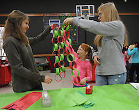 NWA Media/ANDY SHUPE - Sam Rosso, 13, left, Danielle Hammig, 7, and Grier McClard, 13, compare their progress while making construction paper chain Christmas tree decorations Sunday, Dec. 21, 2014, while taking part in a Christmas festival at Good Shepherd Lutheran Church in Fayetteville. The event featured a puppet show, crafts, a nativity photo booth and breakfast.