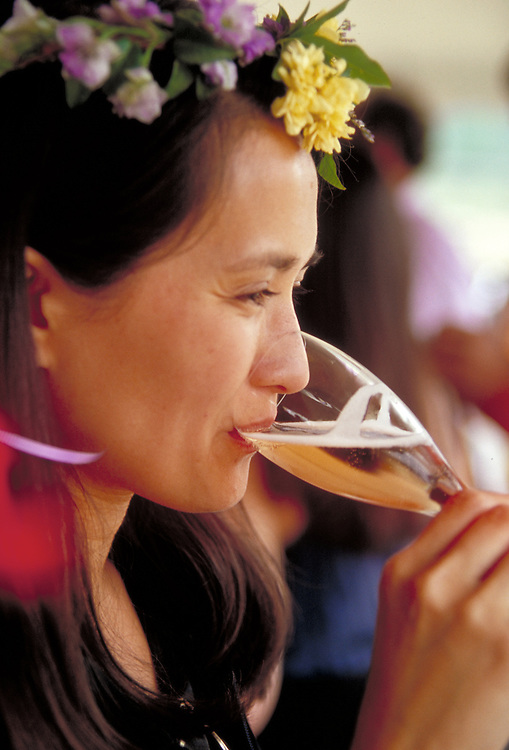 Girl drinking sparkling wine at May Day celebration in Anderson Valley California