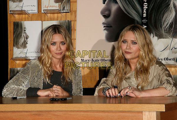 MARY-KATE OLSEN & ASHLEY OLSEN.Sign Copies of ?Influence? at Borders in Westwood , California. in Westwood, California, USA. .November 12th, 2008.half length book twins sisters black grey gray top beige gold dress cardigan coat jacket sitting table .CAP/DVS.©Debbie VanStory/Capital Pictures.