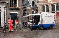Medewerkers van de stadsreiniging maken het Oude Kerksplein in Amsterdam schoon