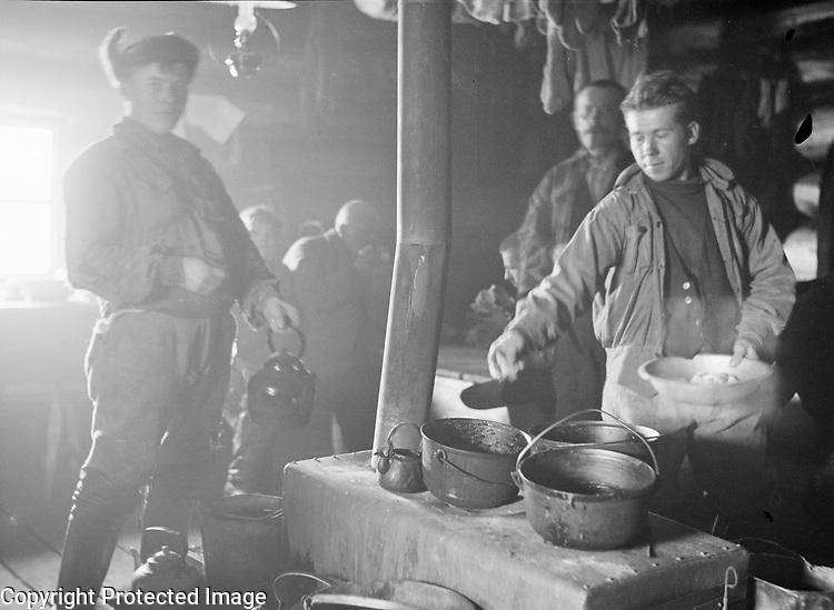 Male foresters cooking on stove in cabin, Finland 1930s